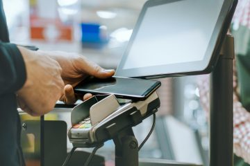 In the Supermarket Close-up Footage of the Man Paying with Smartphone at the Checkout Counter. Using Modern and Convenient Wireless NFC Paying System in Big Mall.